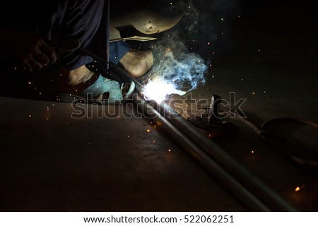Man with protective mask welding metal in dark contrast background