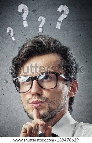 man with question marks over his head - stock photo