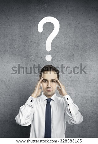 man with questions symbol over head on gray background - stock photo