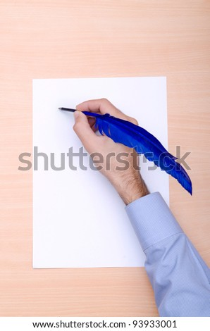 Man with quill writing - stock photo