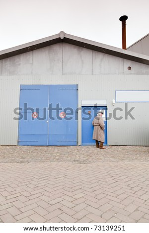 Man with raincoat and hat standing in front of closed door of industrial building. - stock photo