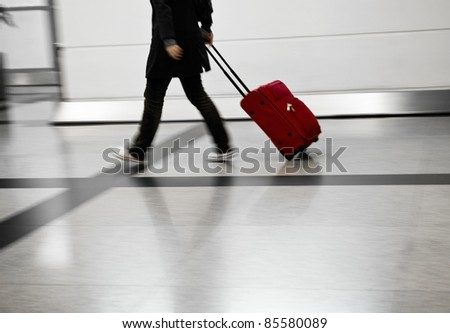 Man with red bags rushing at the airport - stock photo