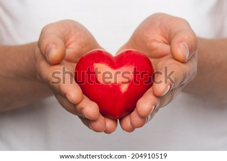 Man with red heart in his hands over body background. - stock photo