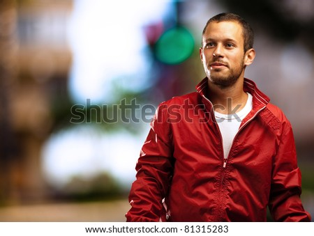 man with red jacket with a city as a background - stock photo