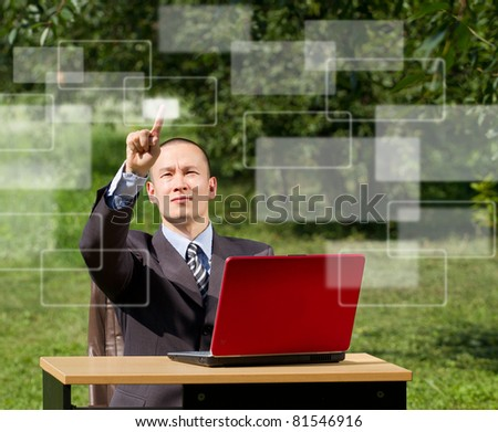man with red laptop working outdoors, pushs the button