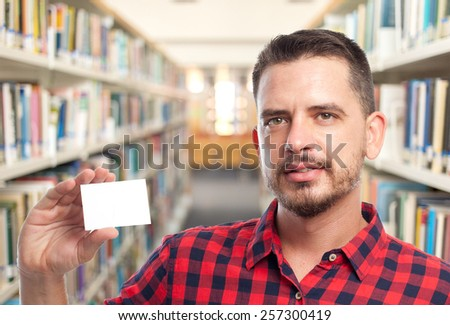 Man with red squares shirt. He is holding a white card. Over library background