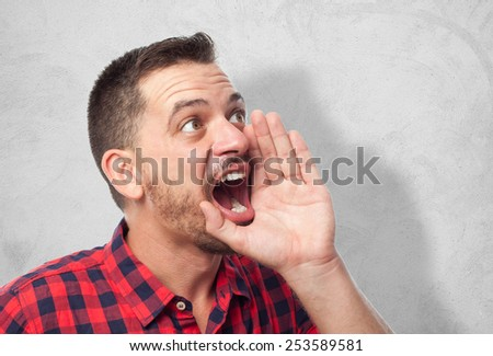 Man with red squares shirt. He is screaming. Over concrete wall - stock photo