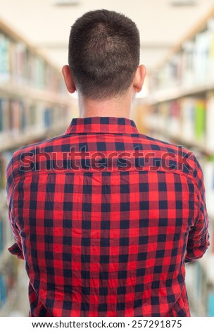 Man with red squares shirt. He is showing his back. Over library background - stock photo