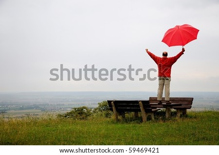 Man with red umbrella at a rainy day raising his arms - stock photo