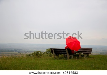 Man with red umbrella sitting on a bench - stock photo