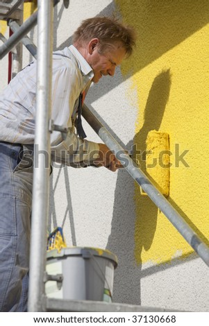 man with roller painting house - stock photo