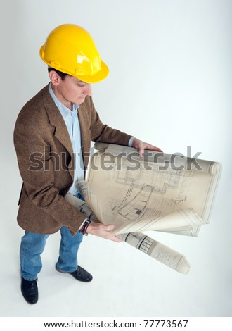 Man with safety helmet looking at architecture blueprints - stock photo