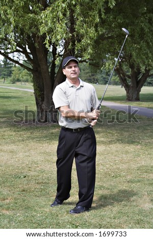 Man with satisfied expression views his golf drive. - stock photo