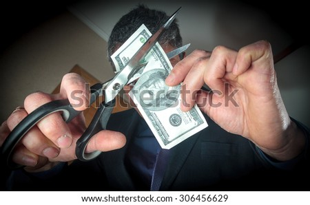 Man with scissors cuts the banknote denominations of 100 dollars( hundred dollar bill). - stock photo