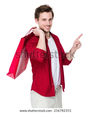 Man with shopping bag and finger point up - stock photo