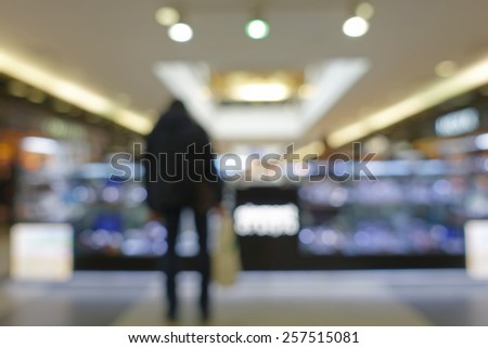 Man with shopping bags standing at the window in a shopping center,shallow depth of focus - stock photo