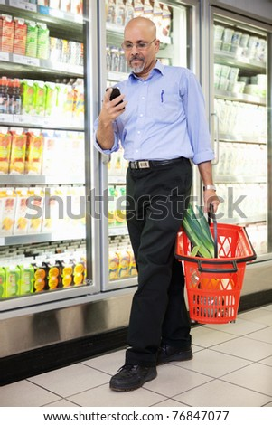 Man with shopping basket looking at cell phone while walking in shopping store - stock photo