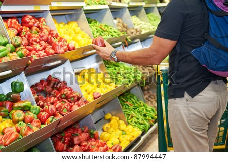 Man with shopping cart during vegetable and fruit shopping at the supermarket - stock photo