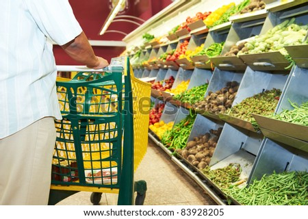 Man with shopping cart during vegetable shopping at the supermarket - stock photo