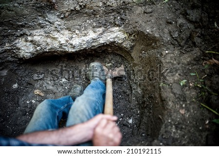 man with shovel and spade working and digging a hole in the ground - stock photo