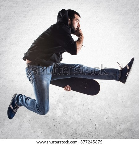 Man with skateboard jumping over textured background