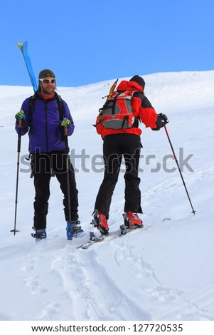 Man with skies on the backpack standing on the snow and woman climbing on touring skies - stock photo