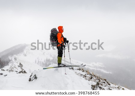 Man with skis and backpack standing on a mountain top