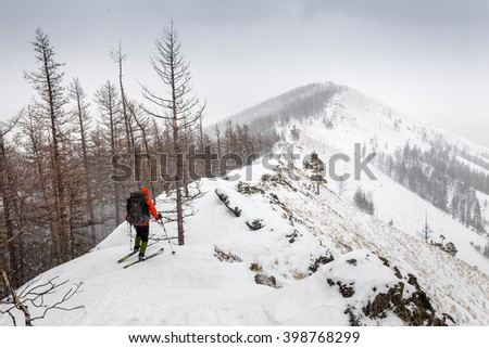 Man with skis and backpack standing on a trail at mountain top