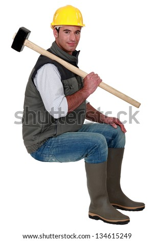 Man with sledge-hammer sat on stool - stock photo