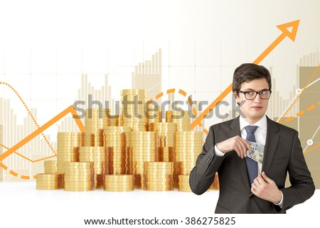Man with sly look putting one hundred dollar banknotes into the chest pocket. Coins and graphs at background. Concept of getting rich. - stock photo