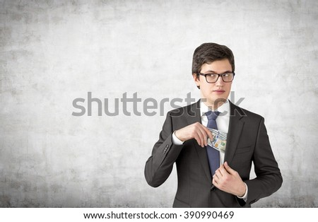 Man with sly look putting one hundred dollar banknotes into the chest pocket. Concrete background. Concept of getting money. - stock photo