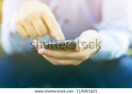 Man with smart phone on hand, blurred background - stock photo