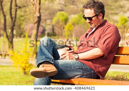 Man with smartphone and coffee sitting alone on a bench in the park in a sunny day