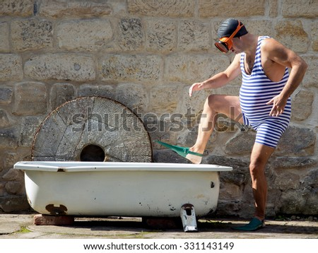 Man with snorkeling gear going to the bathtub outdoor. Holiday home. Man in retro swimsuit want diving in the outdoor bathtub. Retro vintage style swimmer go to tub. Retro diver in the bathtub.. - stock photo