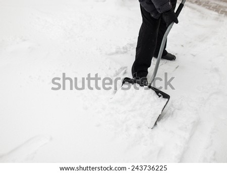 Man with snow shovel cleans sidewalks in winter - stock photo