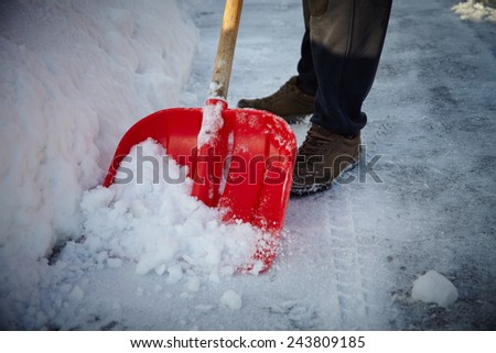 Man with snow shovel cleans sidewalks in winter. Winter time. Latvia. Europe.  - stock photo