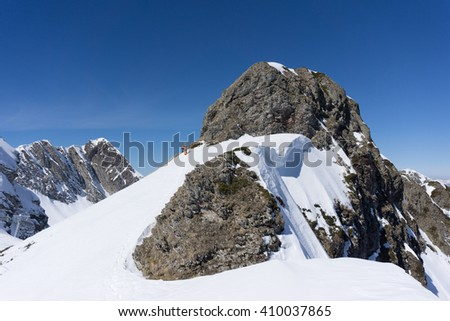 Man with snowboard on top of a mountain, extreme moutaineering. - stock photo