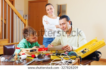 Man with son doing something with the working tool,  woman watching them in home - stock photo