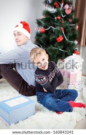 Man with son, Happy man and his son near decorated firtree - stock photo