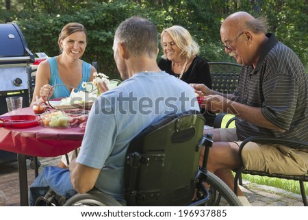 Man with spinal cord injury in wheelchair at family outdoor cookout picnic - stock photo