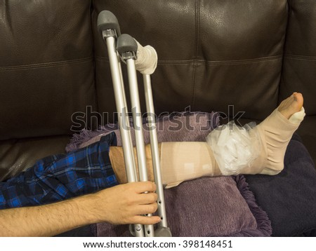 Man With Sprained, Broken, Fractured Ankle Grabs His Crutches - stock photo