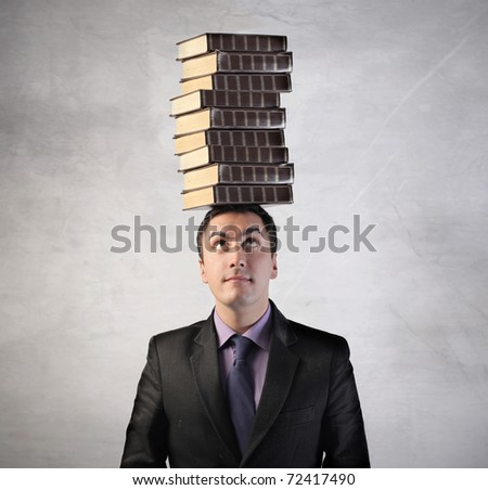 Man with stack of books on his head - stock photo