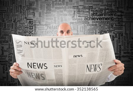 Man with startled expression reading a newspaper - stock photo