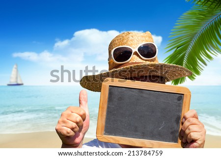 Man with straw hat and sunglasses holds blank slate blackboard with the hands up and showing thumbs up with the Beach in the Background