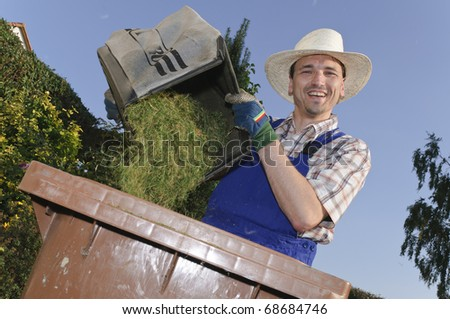 Man with straw hat attacks the organic waste with grass clippings in the garden and laughs at the camera - stock photo