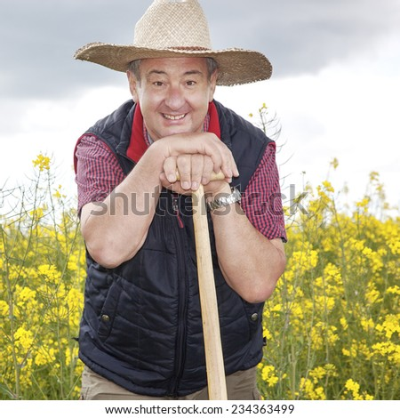 Man with straw hat in rape field - stock photo