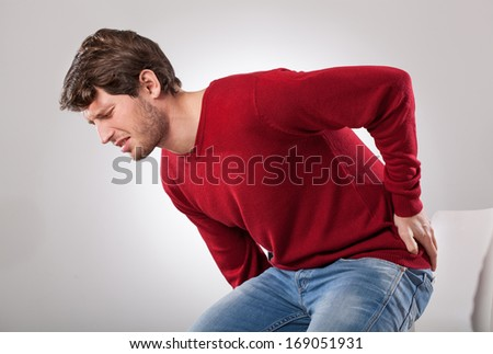 Man with strong backache can't sit on the chair - stock photo