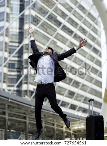 Man with suit jumping with umbrella.