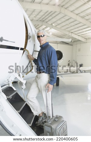 Man with suitcase boarding airplane in hanger