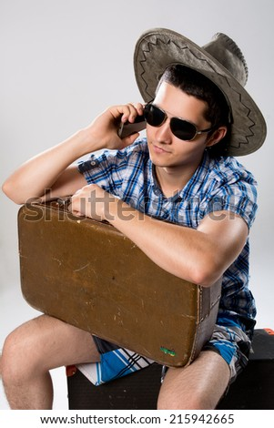 Man with suitcase talking on phone. A young man wearing a hat and sunglasses - stock photo